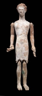 Terracotta figurine with jointed limbs. The arms are movable at the shoulders and the jegs are attached at the knee joint. Each hand holds a pair of krotala; part of those in the left hand are gone. Appears to be clothed. The figure is split down each side. Long interpreted as a doll but may in fact have been a votive. Figurines holding krotala are likely meant to represent dancers. 01.7883